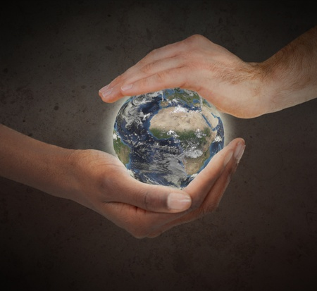 Two hands protecting a glowing planet globe against a white background photo