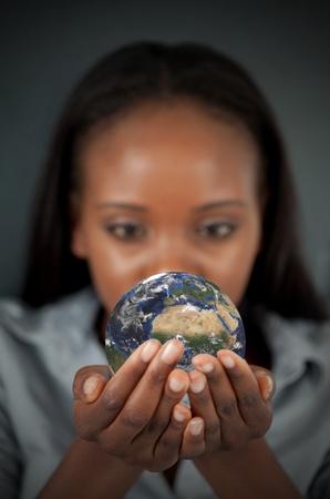 Frau h�lt die Erde vor einem dunklen Hintergrund