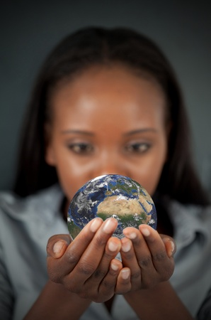 Woman holding the Earth against a dark background photo