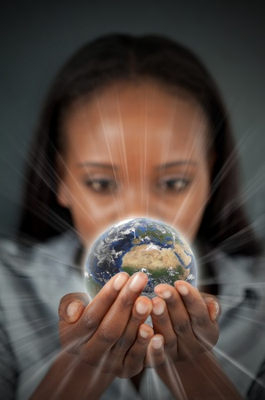 Woman holding a glowing Earth against a dark background photo