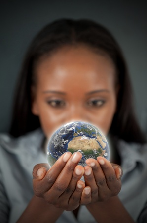 Beautiful woman holding the Earth against a dark background photo