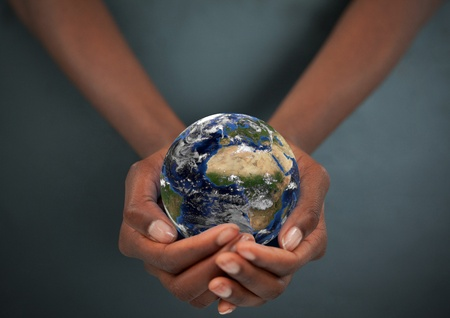 water ecosystem: Feminine hands holding the Earth against a dark background Stock Photo
