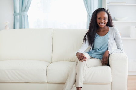 crossed legs: Smiling woman sitting on sofa with legs crossed Stock Photo