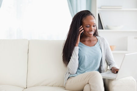 phonecall: Smiling woman with smartphone and notebook on the sofa