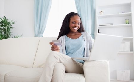 Smiling woman shopping online while sitting on sofa photo