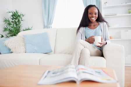 Smiling woman with a cup on the sofa photo
