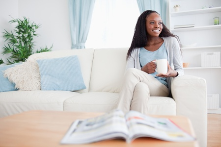 Smiling woman with a cup on the couch photo