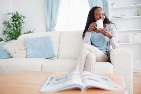 Smiling woman drinking coffee on the sofa photo