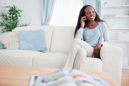 phonecall: Smiling woman on the phone while sitting on sofa