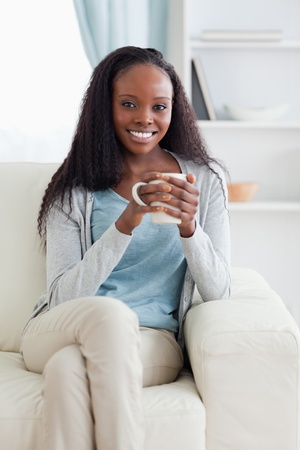 Smiling woman with cup on her sofa photo