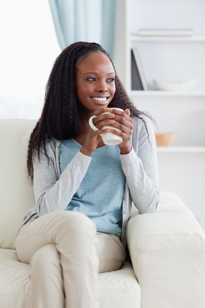 Smiling woman on sofa with a cup photo