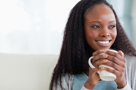 Close up of smiling woman with a cup on sofa photo