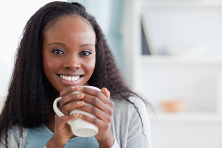 Close up of smiling woman sitting on sofa with a cup photo