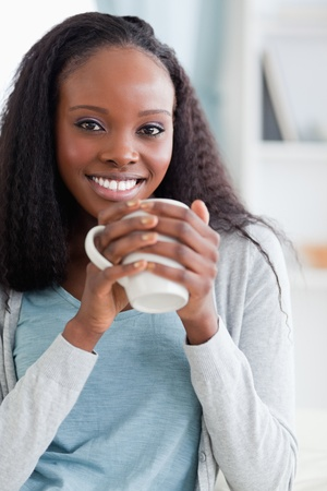 Close up of smiling woman sitting on couch with a cup photo
