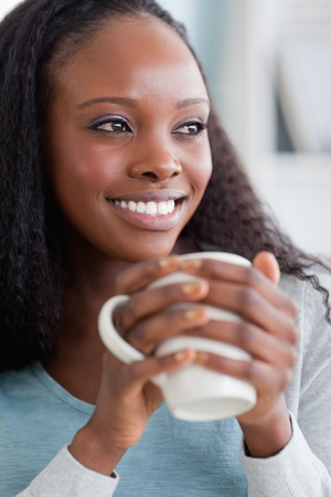 Close up of smiling woman on sofa having coffee photo