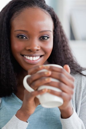 Close up of smiling woman having coffee on couch photo