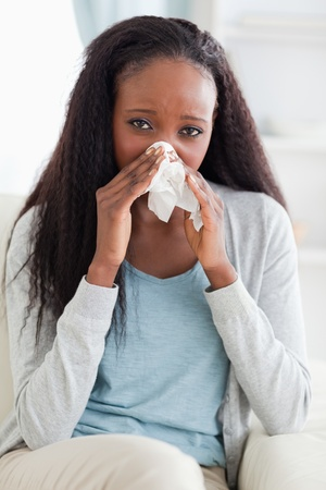 catarrh: Close up of young woman on couch blowing her nose Stock Photo