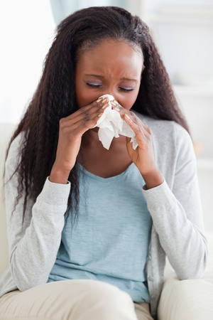 catarrh: Close up of young woman blowing her nose on sofa