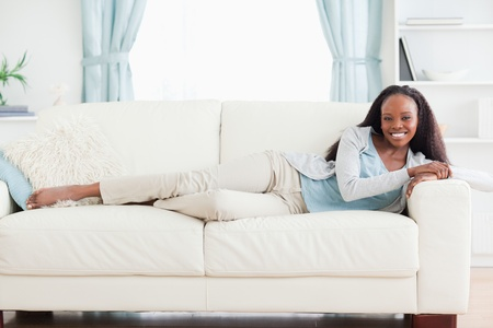 Smiling woman lying on sofa photo