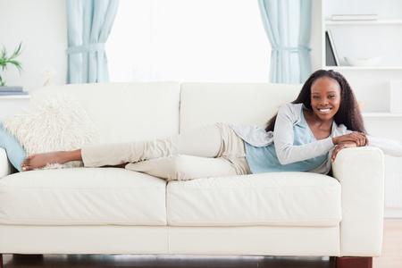 Smiling woman lying on sofa photo