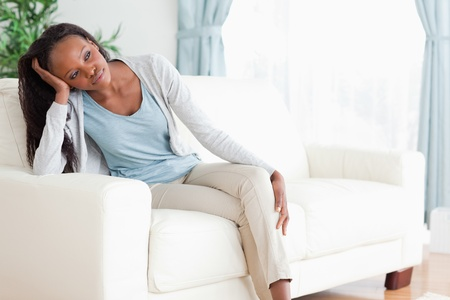 armrest: Young woman on sofa in thoughts Stock Photo