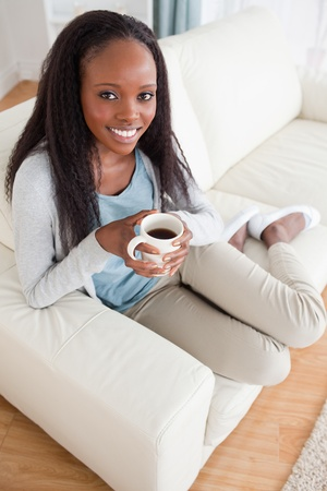 Smiling woman enjoying coffee on couch photo