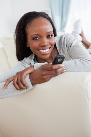 Close up of smiling woman texting on couch Stock Photo - 11620259