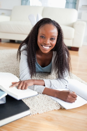 Smiling young woman lying on carpet doing a book review photo