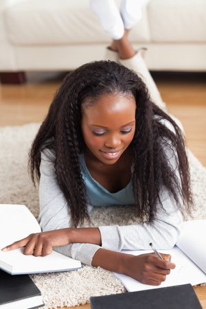 Smiling woman lying on carpet in living room doing homework photo