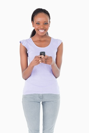 Close up of smiling woman holding cellphone on white background photo