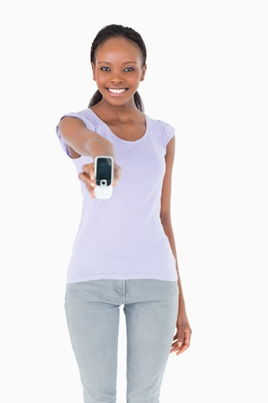Close up of smiling woman presenting her phone on white background photo