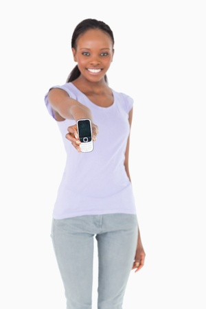 Close up of phone being presented by smiling woman on white background photo