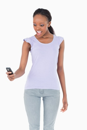 Close up of young woman being surprised by text message on white background photo