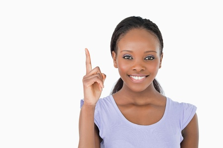 Close up of smiling young woman pointing upwards on white background photo