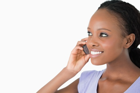 Close up of smiling woman talking on her phone on white background photo
