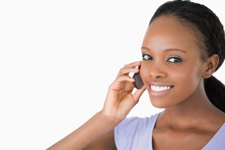 Close up of smiling woman on the phone against a white background Stock Photo - 11619162