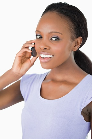 Close up of smiling woman talking on the phone against a white background Stock Photo - 11620318