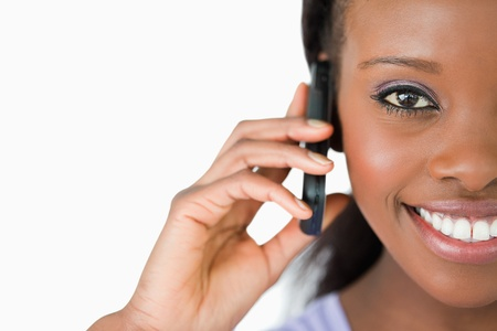 Close up of smiling woman on her phone against a white background photo