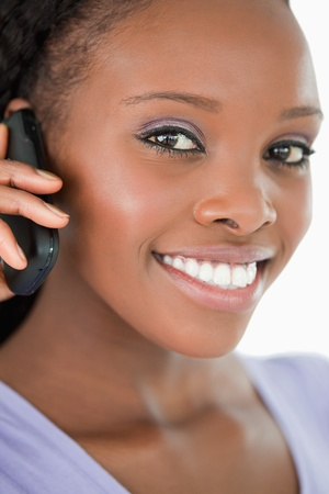 Close up of smiling woman talking on the mobile phone against a white background photo