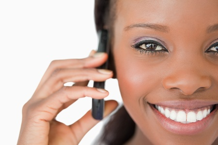 Close up of smiling woman using her mobile phone on white background photo
