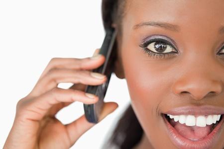 by calling: Cerca de la joven mujer sorprendida en el tel�fono en el fondo blanco
