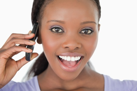 Close up of surprised looking young woman on the phone on white background photo