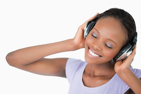 Close up of smiling woman listening to music against a white background photo