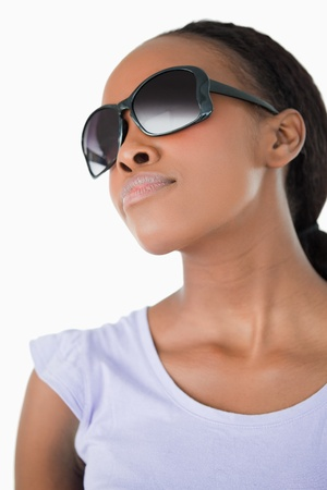 Close up of young woman wearing her sunglasses against a white background photo