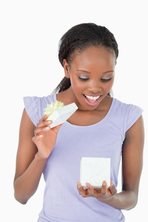 Close up of smiling woman being happy about a present against a white background photo