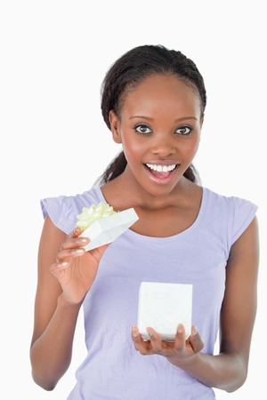 Close up of happy young woman opening a present against a white background photo
