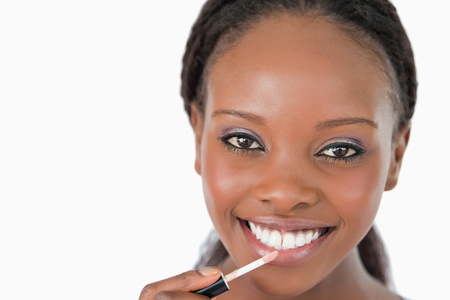Close up of smiling woman applying lip gloss against a white background photo
