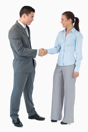 Confident business partner shaking hands against a white background photo