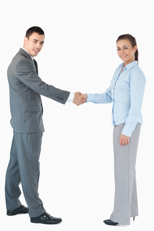Confident business people shaking hands against a white background photo