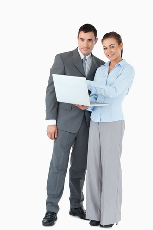 Young business partner with laptop against a white background photo